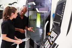 Weiblicher Lehrling, der mit Ingenieur-On CNC-Maschinerie arbeitet stockbilder