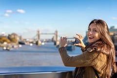 Weiblicher London-Tourist macht Fotos der Turm-Brücke lizenzfreie stockfotografie