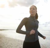 Weiblicher Läufer, der durch den Strand trainiert Stockfotografie