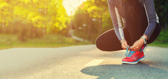 Weiblicher Läufer, der ihre Schuhe sich vorbereiten für einen Stoß bindet Stockbild