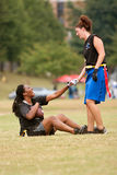 Weiblicher Markierungsfahnen-Fußball-Spieler-Hilfen-Mannschaftskamerad stehen auf stockfotografie