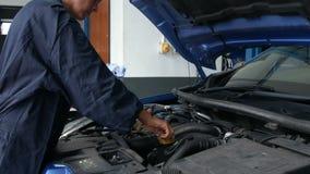 Weiblicher Mechaniker, der Öl in der Maschine überprüft stock video