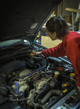 Weiblicher Mechaniker, der Automotor kontrolliert stockbild