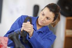 Weiblicher Mechaniker, der Ersatzteil an der Garage aufhebt stockbilder