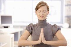 Weiblicher meditierender Büroangestellter Stockbilder