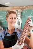 Weiblicher Metzger mit frischer Wurst Stockbild