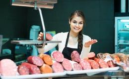 Weiblicher Metzger mit Wurst und Bologna im Fleisch speichern entgegengesetzt lizenzfreie stockfotografie
