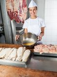 Weiblicher Metzger Showing Egg Yolk in der Schüssel Lizenzfreie Stockfotos