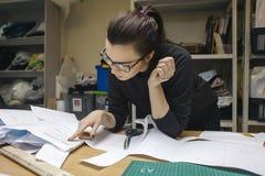 Weiblicher Modedesigner bei der Arbeit im authentischen Werkstattinnenraum Lizenzfreie Stockfotografie