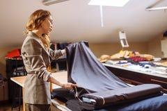 Weiblicher Modedesigner, der an dem Entsprechen des Gewebes mit Dressmakingzusätzen auf Tabelle arbeitet stockfoto