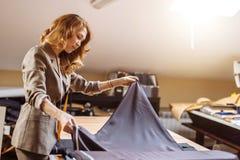 Weiblicher Modedesigner, der an dem Entsprechen des Gewebes mit Dressmakingzusätzen auf Tabelle arbeitet stockbild