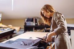 Weiblicher Modedesigner, der an dem Entsprechen des Gewebes mit Dressmakingzusätzen auf Tabelle arbeitet lizenzfreie stockfotografie