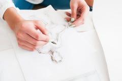 Weiblicher Modedesigner, der an der Werkstatt skizziert Lizenzfreie Stockbilder