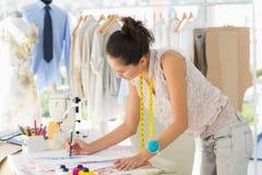 Weiblicher Modedesigner, der an ihren Designen arbeitet Lizenzfreie Stockfotografie