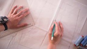 Weiblicher Modedesigner, der mit Musterausschnitt am Studio arbeitet lizenzfreies stockbild