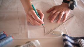 Weiblicher Modedesigner, der mit Musterausschnitt am Studio arbeitet stockfotografie