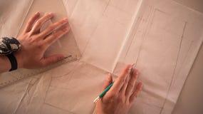 Weiblicher Modedesigner, der mit Musterausschnitt am Studio, Draufsicht arbeitet stockfotos