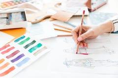 Weiblicher Modedesigner, der an Skizzen mit Farbe arbeitet Stockfotografie