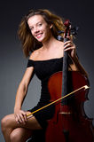 Weiblicher musikalischer Spieler gegen dunklen Hintergrund Lizenzfreie Stockbilder
