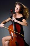 Weiblicher musikalischer Spieler gegen dunklen Hintergrund Stockfoto