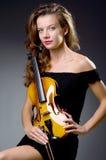 Weiblicher musikalischer Spieler gegen dunklen Hintergrund Lizenzfreie Stockfotos