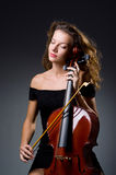 Weiblicher musikalischer Spieler gegen dunklen Hintergrund Lizenzfreies Stockfoto