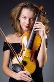 Weiblicher musikalischer Spieler gegen dunklen Hintergrund Stockbild