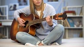 Weiblicher Musiker, der die Gitarre auf Hauptsofa, die Melodie genießend abstimmt und üben stockfotos