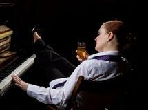 Weiblicher Musiker kleidete in einer Mann ` s Klage an, die nahe bei dem Klavier sitzt und trinkt Champagner stockfotografie