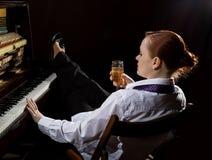 Weiblicher Musiker kleidete in einer Mann ` s Klage an, die nahe bei dem Klavier sitzt und trinkt Champagner lizenzfreies stockbild