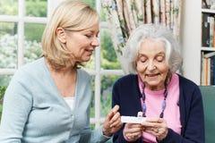Weiblicher Nachbar, welche älterer Frau mit Medikation hilft stockbild