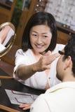 Weiblicher Optometriker Assisting Patient In, das Schauspiele wählt stockfotos