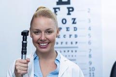 Weiblicher Optometriker, der Ophthalmoskop hält Lizenzfreie Stockfotografie
