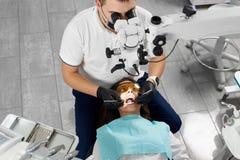 Weiblicher Patient der männlichen Zahnarztfestlichkeiten, der neue Technologien des Mikroskopgebrauches einsetzt Lizenzfreie Stockfotos
