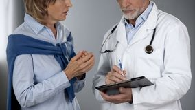 Weiblicher Patient, der spricht, um über die Testergebnisse zu behandeln, entsetzt durch Diagnose lizenzfreie stockfotografie