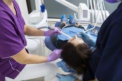 Weiblicher Patient, der von den Zahnärzten in der Klinik unterstützt wird stockfotografie