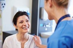 Weiblicher Patient, der von Doktor In Hospital Room versichert wird Stockbilder
