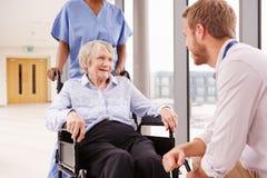 Weiblicher Patient Doktor-Talking To Senior im Rollstuhl lizenzfreie stockfotos