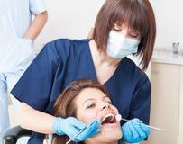 Weiblicher Patient mit den perfekten Zähnen, die auf Zahnarztstuhl sitzen Lizenzfreies Stockfoto