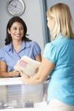 Weiblicher Patient mit Empfangsdamen-In Doctors Waiting-Raum Lizenzfreie Stockfotos