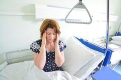 Weiblicher Patient mit Kopfschmerzen auf Bett in der Krankenstation stockfotografie
