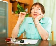 Weiblicher Pensionär, der die Finanzarbeit Innen erledigt Stockbild