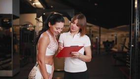 Weiblicher persönlicher Trainer, der mit einer Klientin in einer Turnhalle unter Verwendung einer Tablette für Anmerkungen sprich stock footage