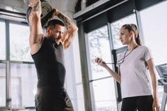 weiblicher persönlicher Trainer, der Timer-Weilesportler verwendet stockfoto