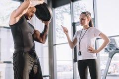 weiblicher persönlicher Trainer, der Weilesportler zählt lizenzfreies stockbild
