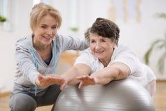 Weiblicher Physiotherapeut, der mit älterem Patienten in der Klinik ausarbeitet lizenzfreies stockfoto