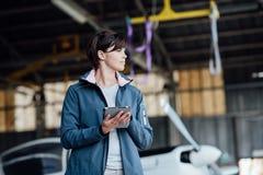 Weiblicher Pilot, der eine digitale Tablette verwendet lizenzfreie stockfotos