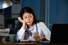 Weiblicher Praktiker, der im Büro unter Verwendung des Smartphone arbeitet Stockbild