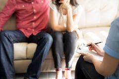 Weiblicher Psychologe, der Anmerkungen auf Therapie-Sitzung macht Stockfotos