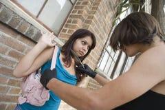 Weiblicher Räuber, der eine Frau mit Messer erschrickt Stockfotografie